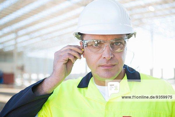 Bauherr mit Schutzbrille zum Einsetzen von Gehörschutzstöpseln auf der Baustelle