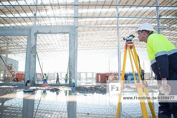 Vermesser mit Stativ und Wasserwaage auf der Baustelle