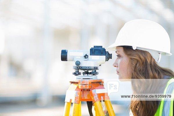 Vermessungsingenieurin beim Durchblick auf der Baustelle