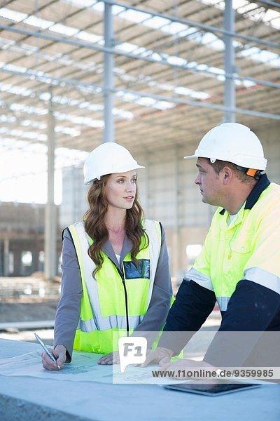 Bauleiter und Architekt mit digitalem Tablett und Bauplan auf der Baustelle