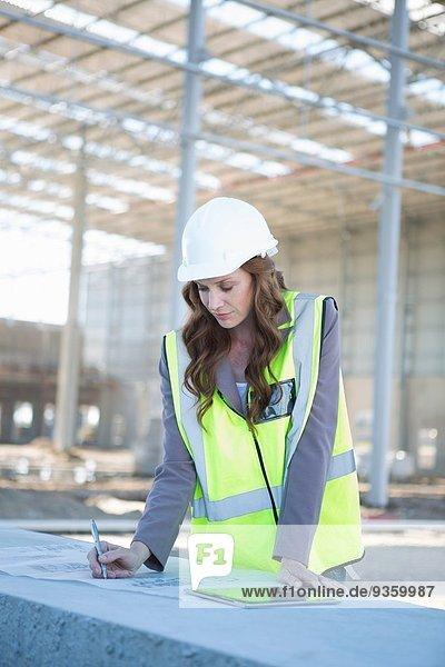 Architekt beim Anpassen des Bauplans auf der Baustelle