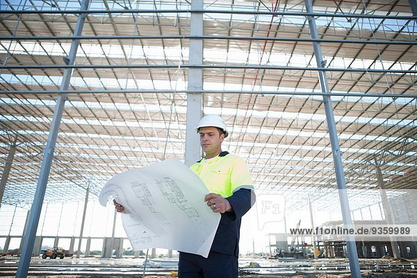 Bauleiter blickt auf den Bauplan auf der Baustelle herab