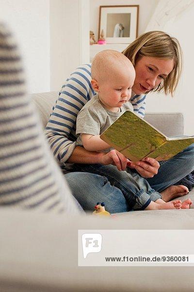 Reife Mutter liest Märchenbuch für die kleine Tochter auf dem Sofa im Wohnzimmer.