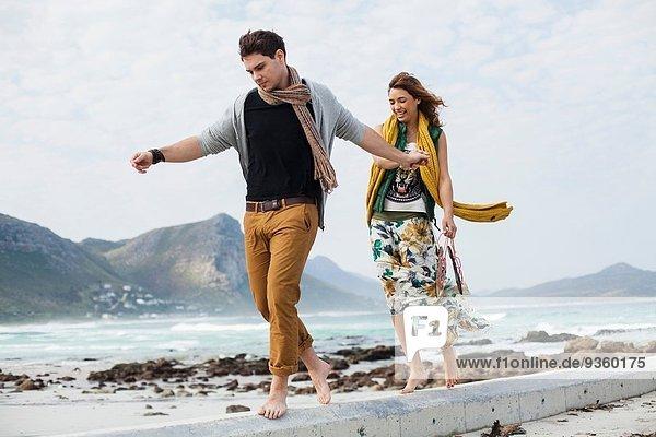 Junges Paar  das am Strand entlanggeht  Kapstadt  Westkap  Südafrika