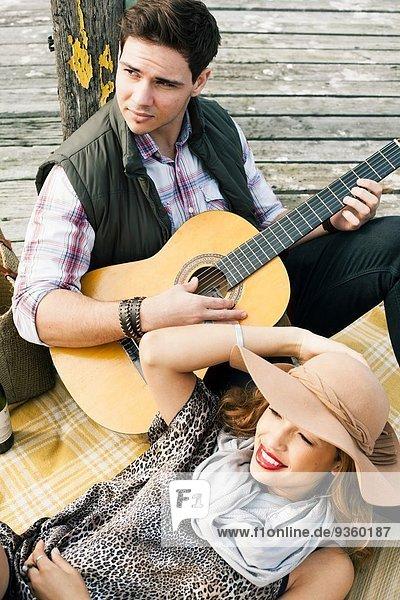 Junges Paar mit Akustikgitarre am Pier liegend