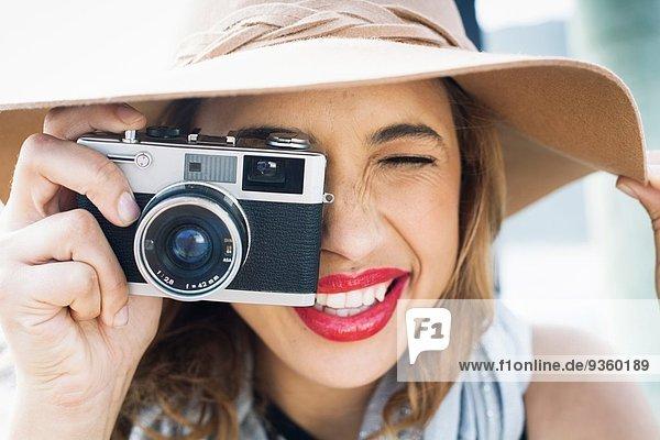 Nahaufnahme einer glamourösen jungen Frau mit Filmkamera