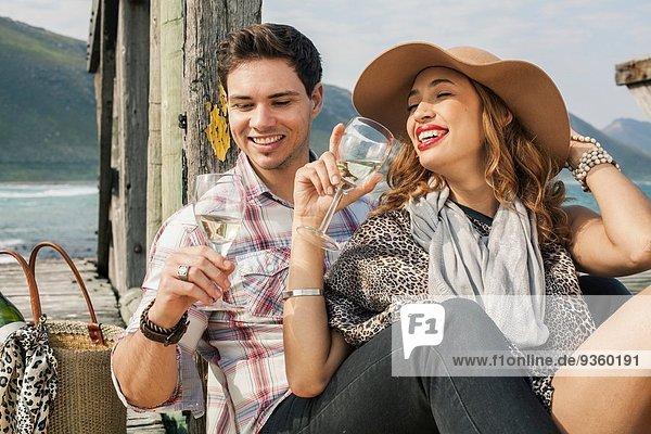 Junges Paar trinkt Wein am alten Pier  Kapstadt  Westkap  Südafrika
