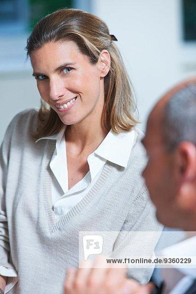Portrait einer Geschäftsfrau neben einem Amtskollegen
