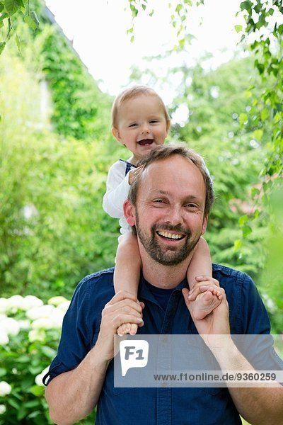Porträt eines Mädchens  das auf den Schultern des Vaters im Garten sitzt
