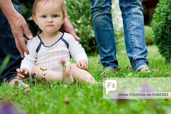 Porträt eines kleinen Mädchens auf dem Rasen sitzend und starrend