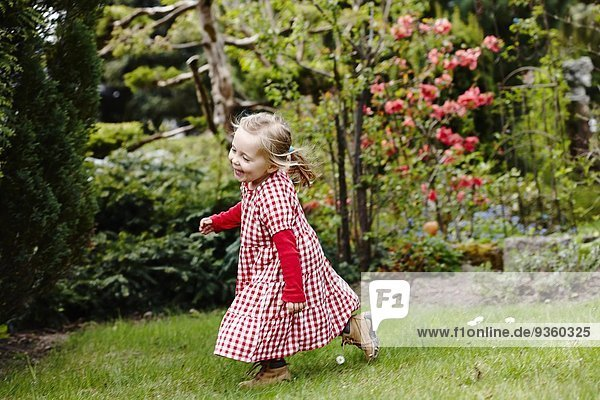 Junges Mädchen im Gingham-Kleid  das im Garten läuft