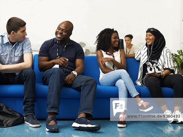Männlicher Dozent im Gespräch mit Studenten im College