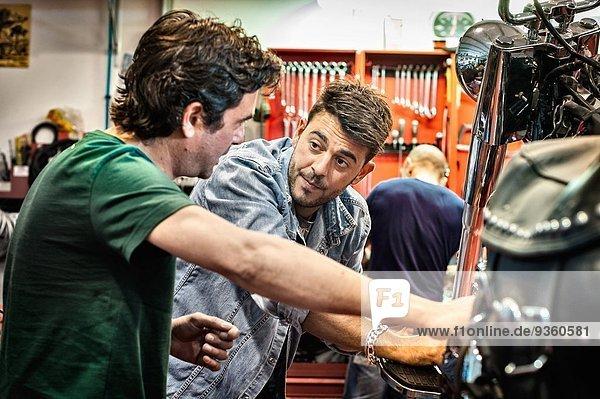 Männliche Mechaniker im Gespräch in der Motorradwerkstatt
