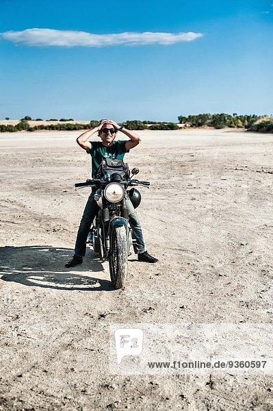 Mittlerer erwachsener Mann auf dem Motorrad auf trockener Ebene  Cagliari  Sardinien  Italien