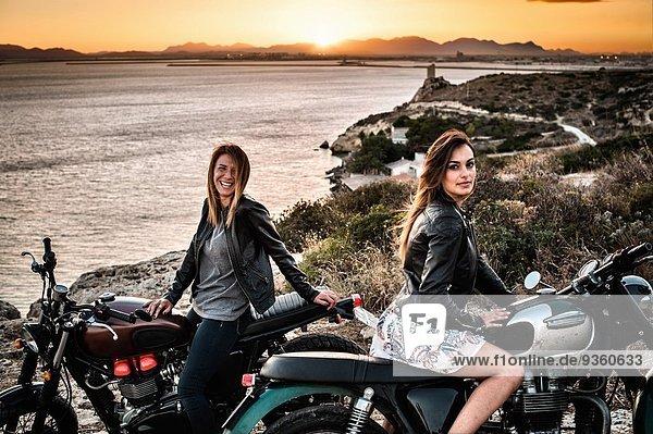 Portrait von zwei Motorradfahrerinnen an der Küste bei Sonnenuntergang  Cagliari  Sardinien  Italien
