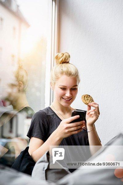 Junge Frau liest Texte auf dem Smartphone im Fensterplatz