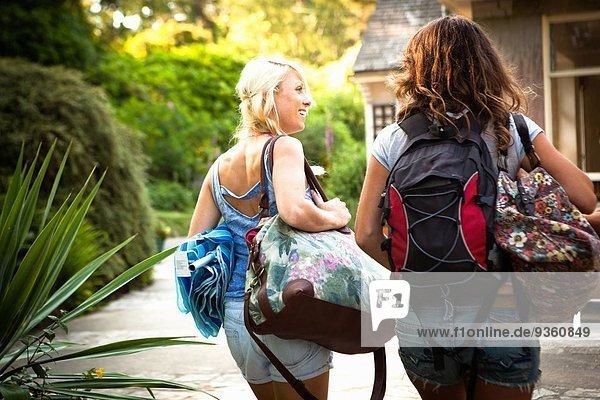 Rückansicht von zwei Freundinnen  die mit Rucksack und Taschen unterwegs sind.