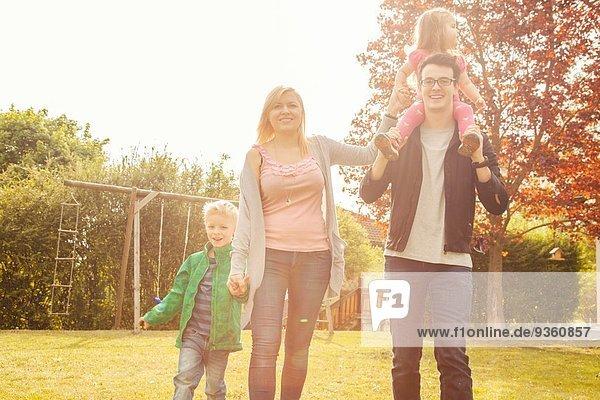 Family in garden  swings in background