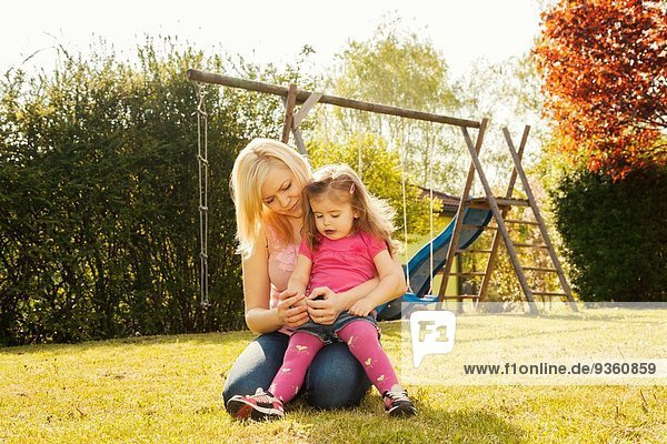 Mother and daughter in garden  swings in background