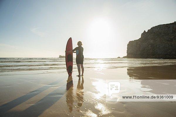 Silhouettierte Seniorin am Strand stehend mit Surfbrett  Camaret-sur-mer  Bretagne  Frankreich
