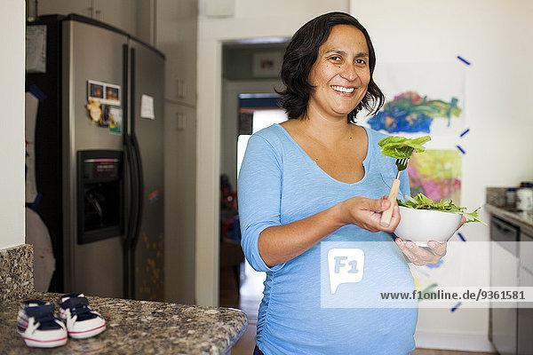 Frau Hispanier Küche Salat Schwangerschaft essen essend isst