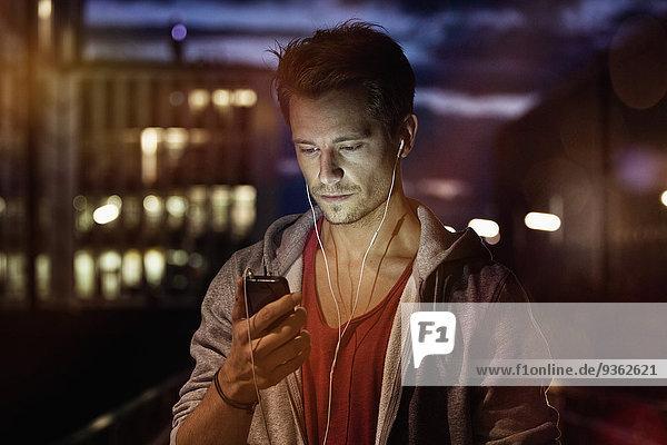 Porträt eines jungen Mannes mit Smartphone und Kopfhörer beim Musikhören bei Nacht