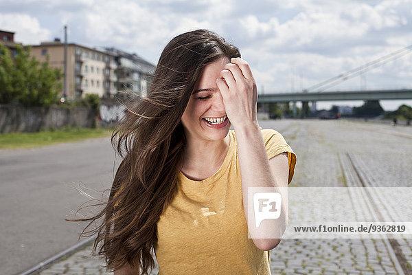 Deutschland  Nordrhein-Westfalen  Köln  Porträt der lachenden jungen Frau mit der Hand im Gesicht