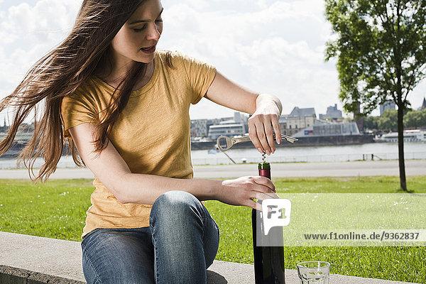 Deutschland  Köln  junge Frau sitzt vor dem Rhein und öffnet Rotweinflasche