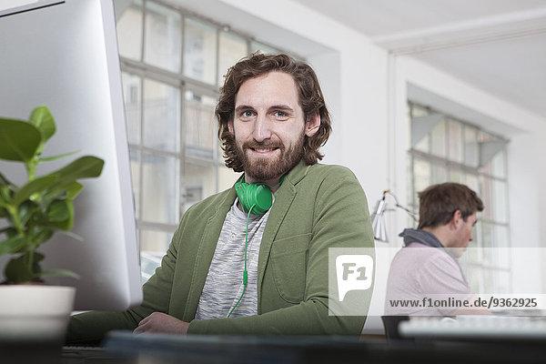 Porträt eines lächelnden jungen Mannes am Schreibtisch in einem Kreativbüro