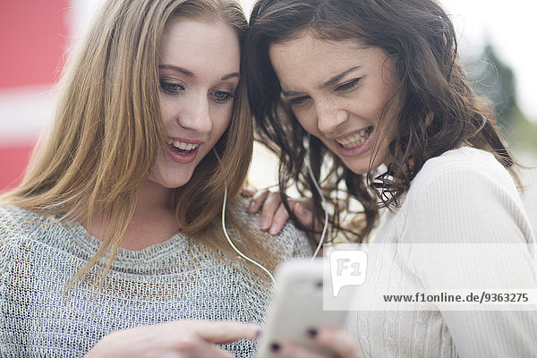 Two female friends listening music with earphones
