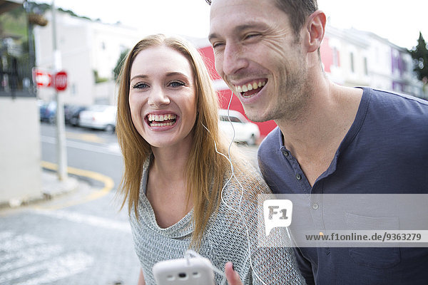 Young couple listening music with earphones