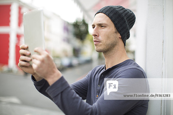 Portrait of young man taking a selfie with his digital tablet