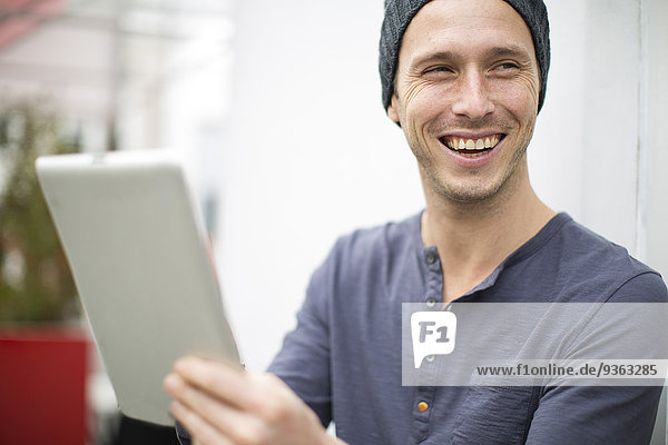 Portrait of smiling young man with digital tablet
