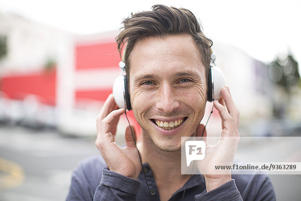 Portrait of smiling young man listening music with headphones
