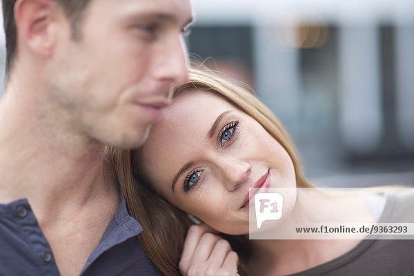 Portrait of happy young woman with head on shoulder of her boyfriend