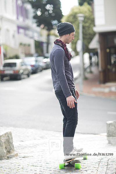 Young man standing on his skateboard on sidewalk