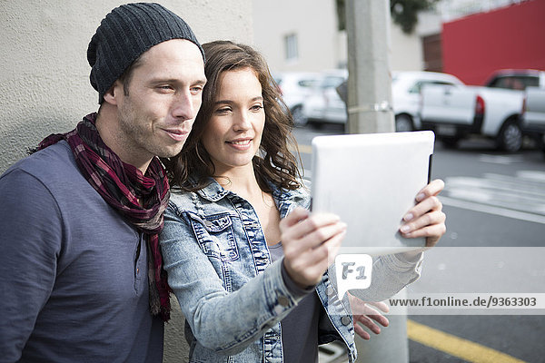Young couple taking a selfie with digital tablet