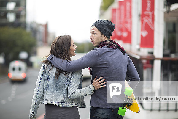 Young couple walking arm in arm on the street