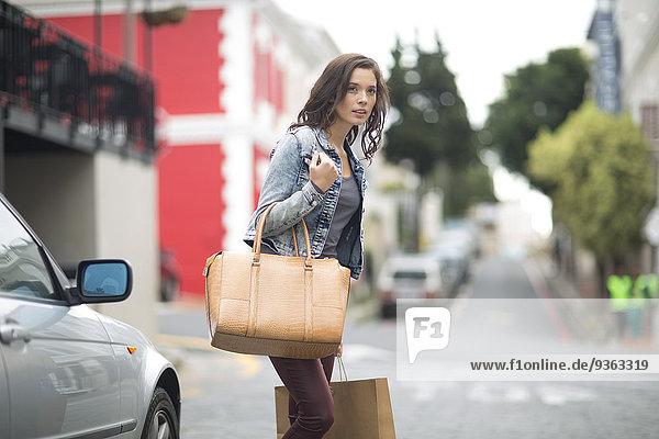 Frau mit Einkaufstasche mit Blick auf die Straße