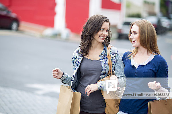 Two female friends with shopping bags walking on the street