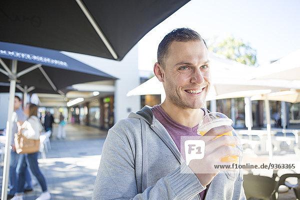 Porträt eines lächelnden Mannes mit einem Erfrischungsgetränk