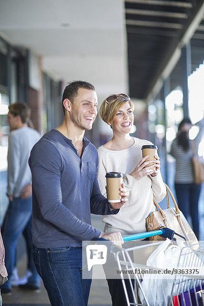 Lächelndes Paar mit Kaffee zum Einkaufsbummel
