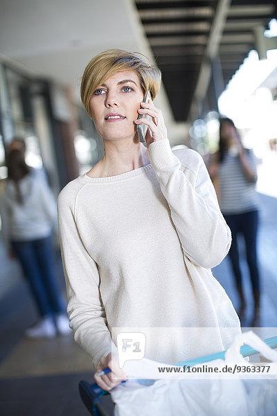 Porträt einer Frau mit Taschen im Einkaufswagen beim Telefonieren