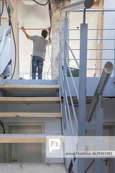Mann renoviert Haus