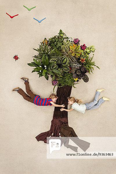 Junge und Mädchen halten sich an einem Baum fest