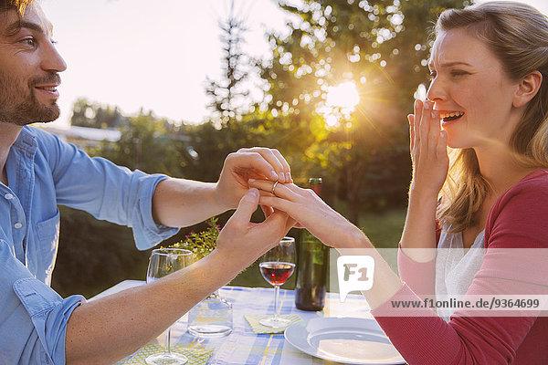 Mann mit Ring am Finger der Frau beim Abendessen