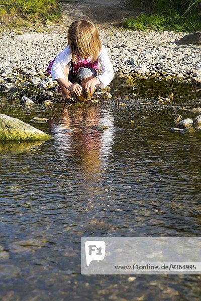 Little girl playing at riverside