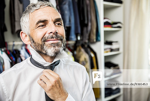 Portrait of smiling businessman binding tie at his walk-in closet