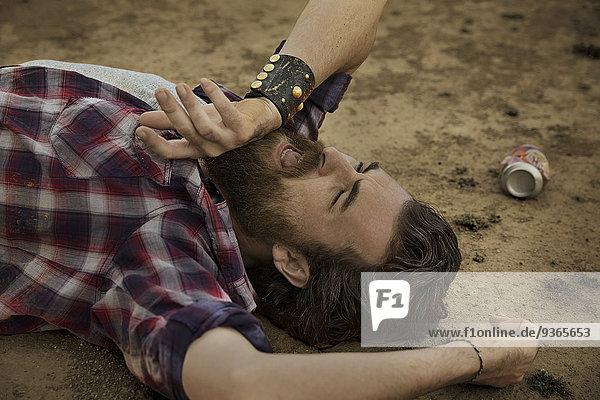 Mann mit Vollbart auf dem Boden liegend