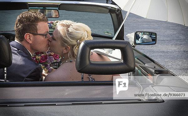 Porträt eines Brautpaares beim Küssen in einem Cabriolet